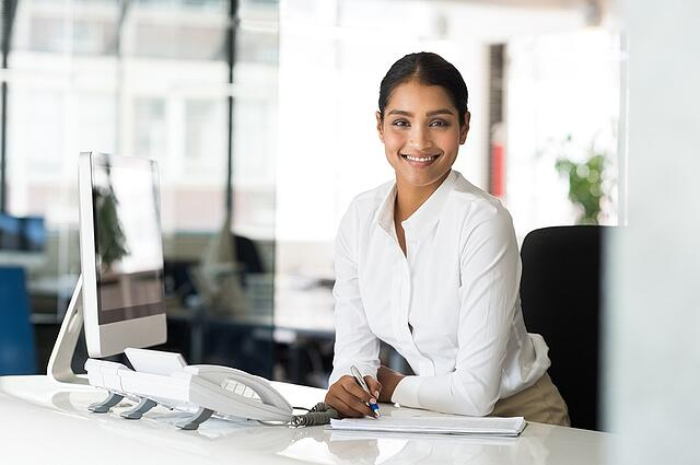 Smiling East Asian Professional woman at desk