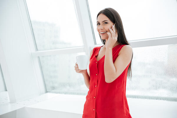 Smiling woman in d-style red on phone with coffee mug