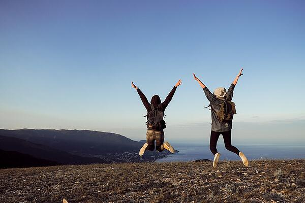 Two-Female-Travelers-Jumping on mountain top