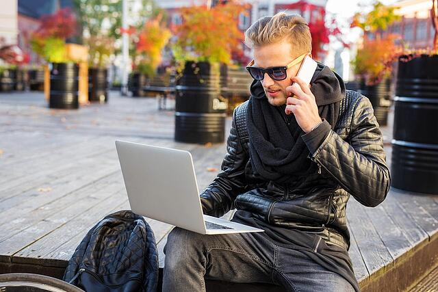 Millennial on phone and working on laptop