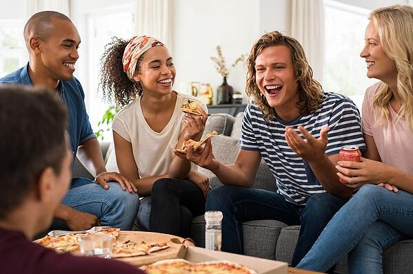 Small group of younger people eating pizza and having fun