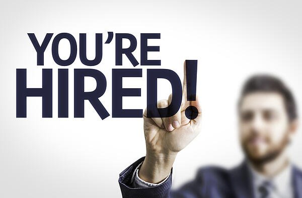 Business man pointing to transparent board with text Youre Hired!