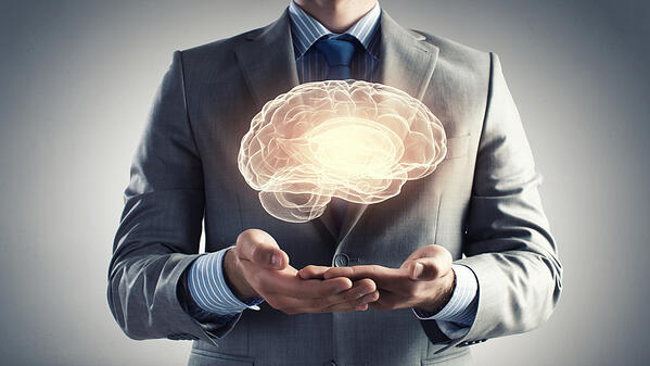 Close up of businessman holding digital image of brain in palm