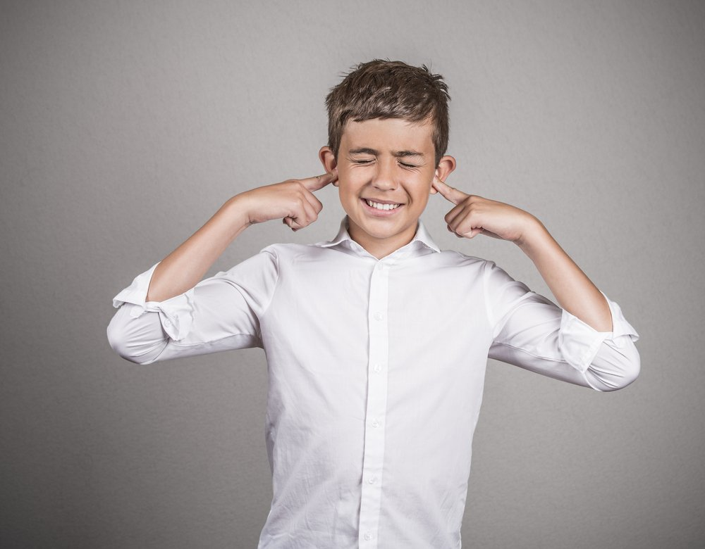a young boy plugging his ears to not listen
