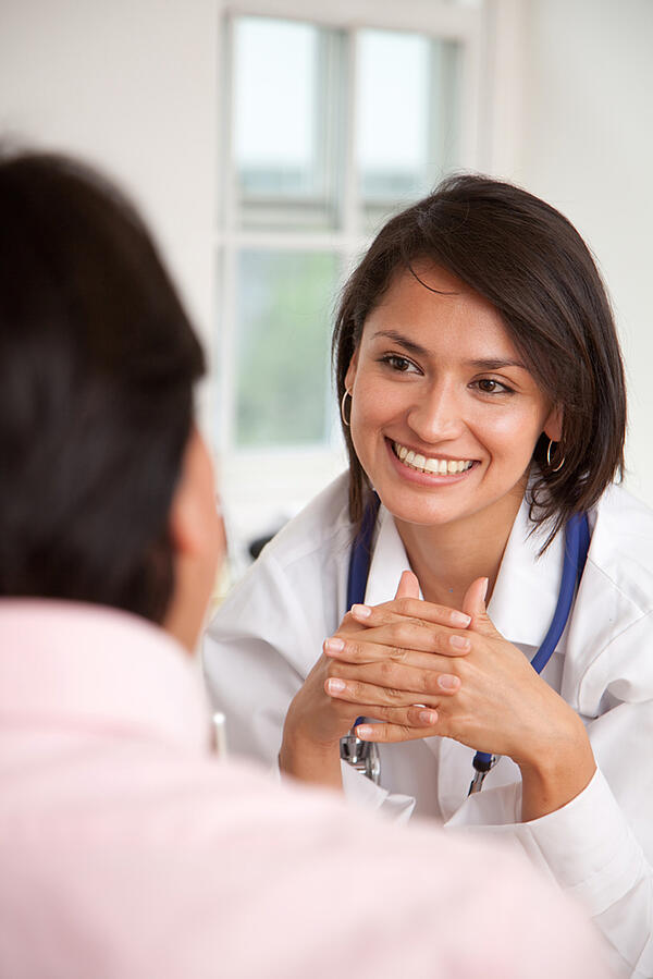 Doctor listening to a patient at her practice