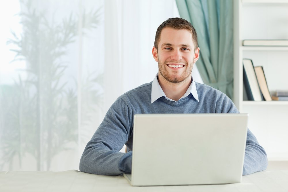 Happy smiling young businessman working in his home office