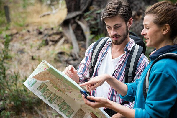Hiker couple looking at map in forest