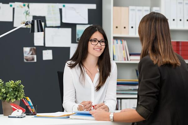 Two young businesswomen having a meeting in the office sitting at a desk having a discussion with focus to a young woman wearing glasses-1