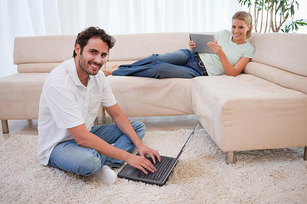 Woman using a tablet computer while her boyfriend is using a notebook in their living room