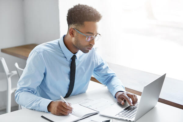 bigstock-Handsome-Young-Dark-skinned-Man in c-style blue on computer with pen and notebook