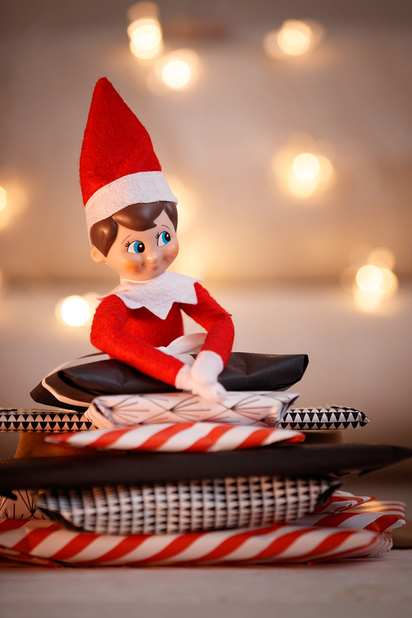 Elf on a shelf sitting on presents
