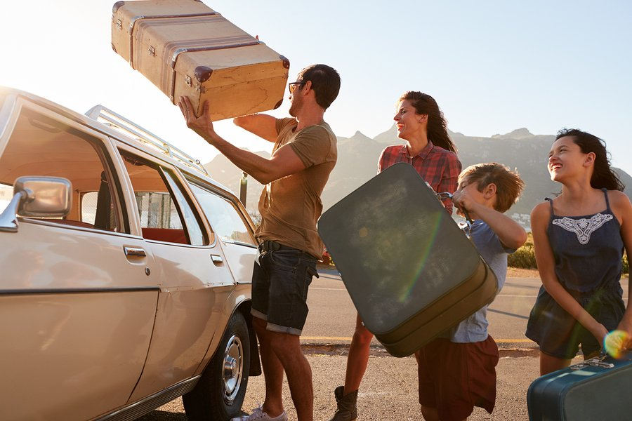 Family loading car for road trip vacation