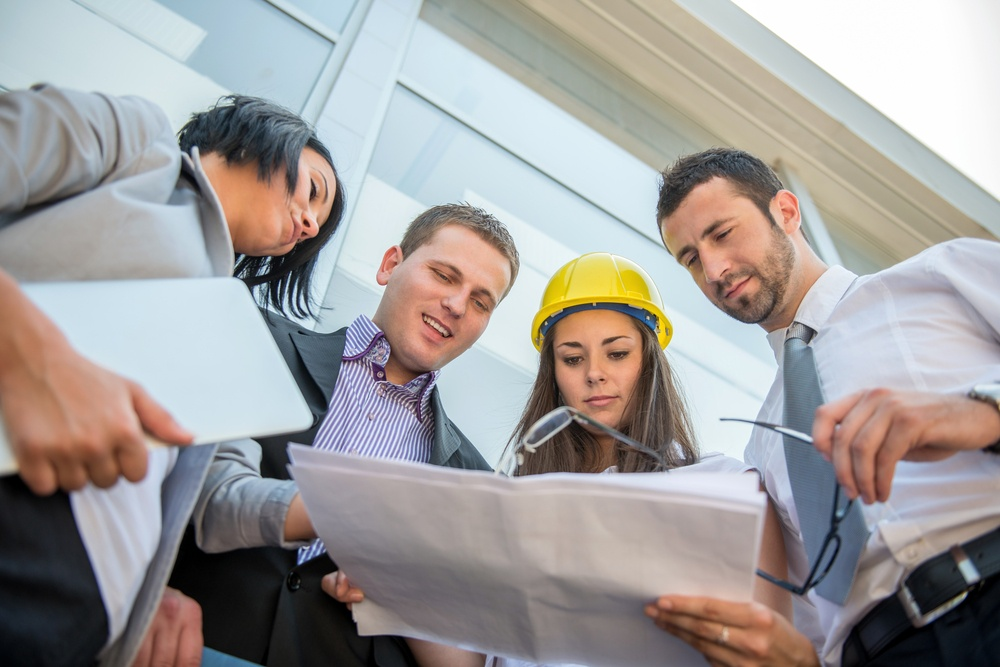 Business people reviewing construction plans in front of building