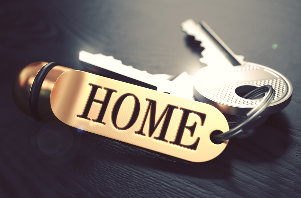 Keys and Golden Keyring with the Word Home over Black Wooden Table with Blur Effect. Toned Image.