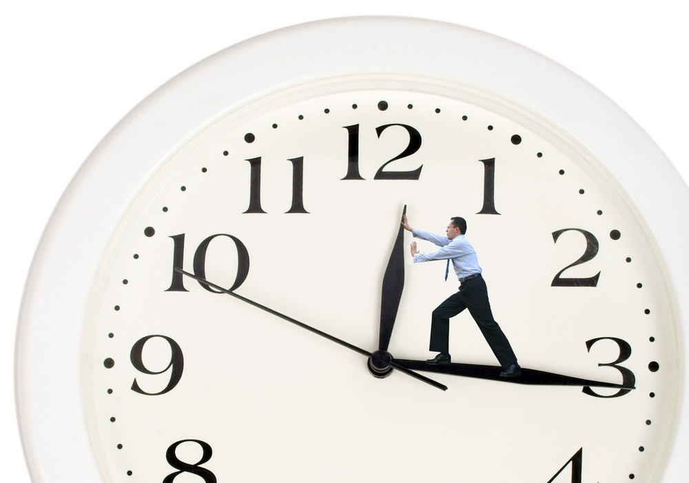 Time management , clock hands pushed back by a man