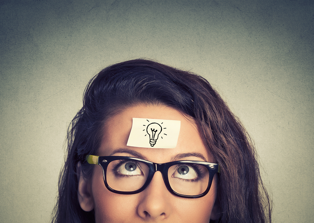 lady with a piece of paper with a lightbulb drawn on it on her forehead